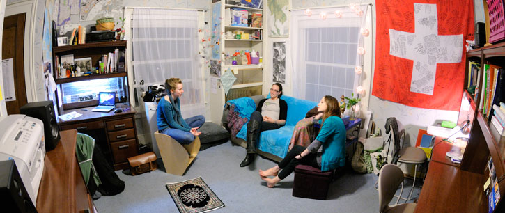 three students sitting in their dorm room