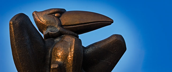 bronze jayhawk statue against blue sky