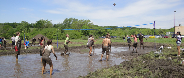 Students playing mud volleyball