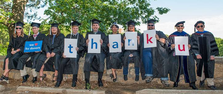 Students and faculty at commencement holding up Thank You signs